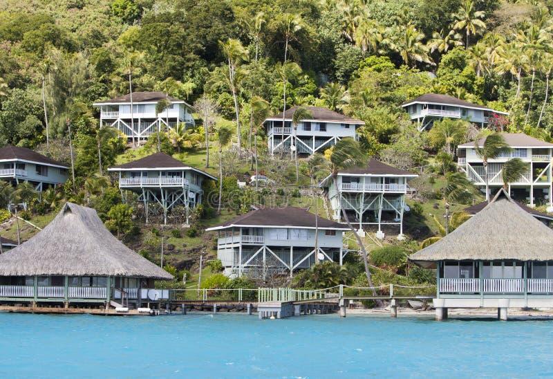 Inclinação do monte pelo mar e pelos alojamentos na inclinação polynesia foto de stock royalty free