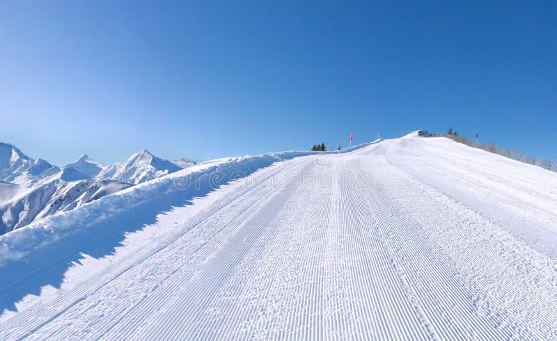 Inclinação perfeitamente preparada do esqui com montanhas fotografia de stock