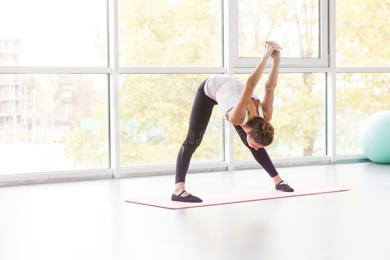 Inclinazione della donna giù, facendo esercizio di forma fisica fotografia stock