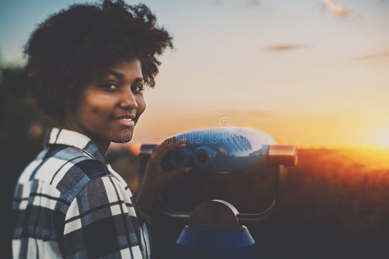 Inclinazione-spostamento che spara alla ragazza nera vicino a binoculare immagini stock