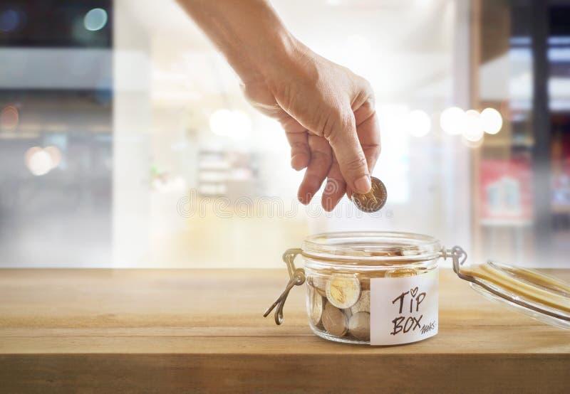 Incline la caja, moneda en el bol de vidrio en el frente del café del espejo imagenes de archivo