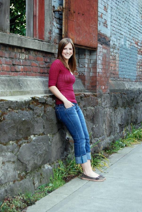 Inclinzione teenager contro la parete - verticale, sorridente fotografia stock libera da diritti