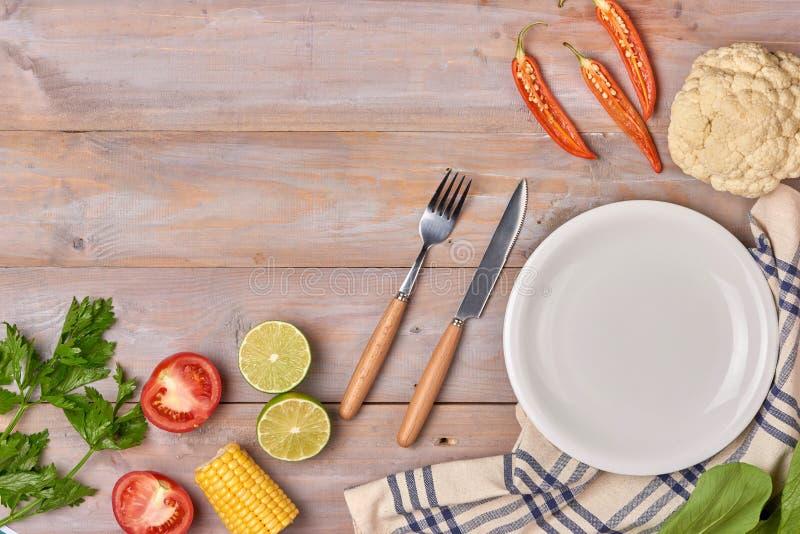 Includa le verdure organiche fresche ed il piatto bianco sul pavimento di legno fotografie stock