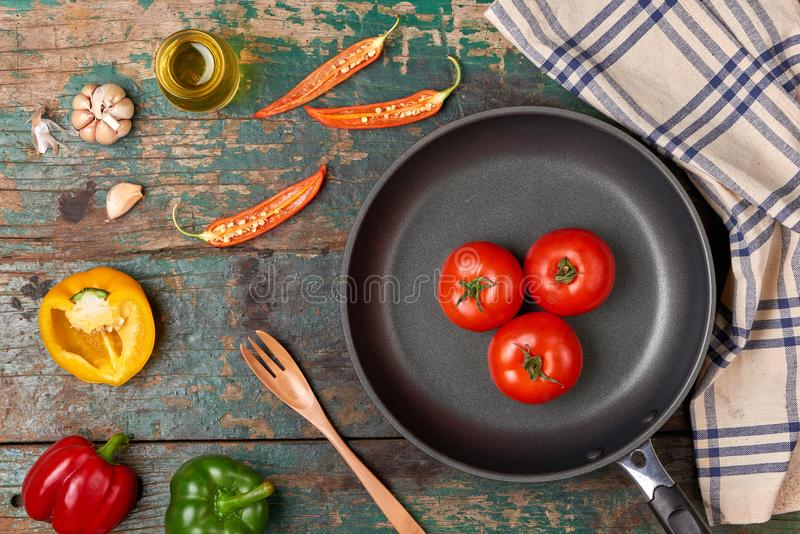 Include fresh organic vegetables and frypan on wooden floor royalty free stock photo