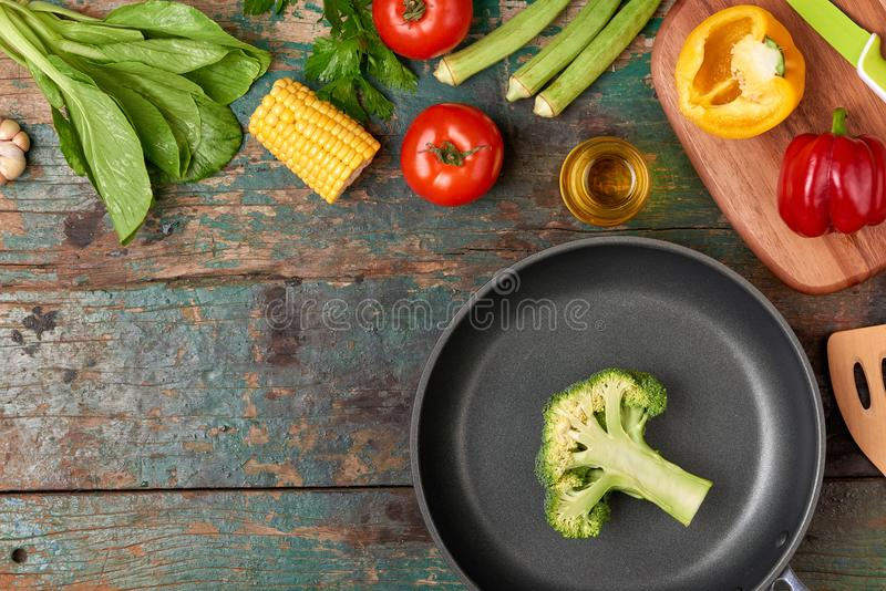 Include fresh organic vegetables and frypan on wooden floor.  stock photo