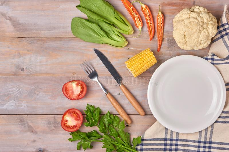 Include fresh organic vegetables and white plate on wooden floor stock photos