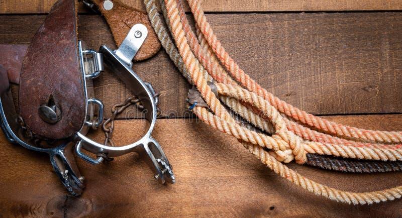 incluing套索踢马刺和一个传统草帽在木板条背景的美国牛仔项目 免版税库存照片