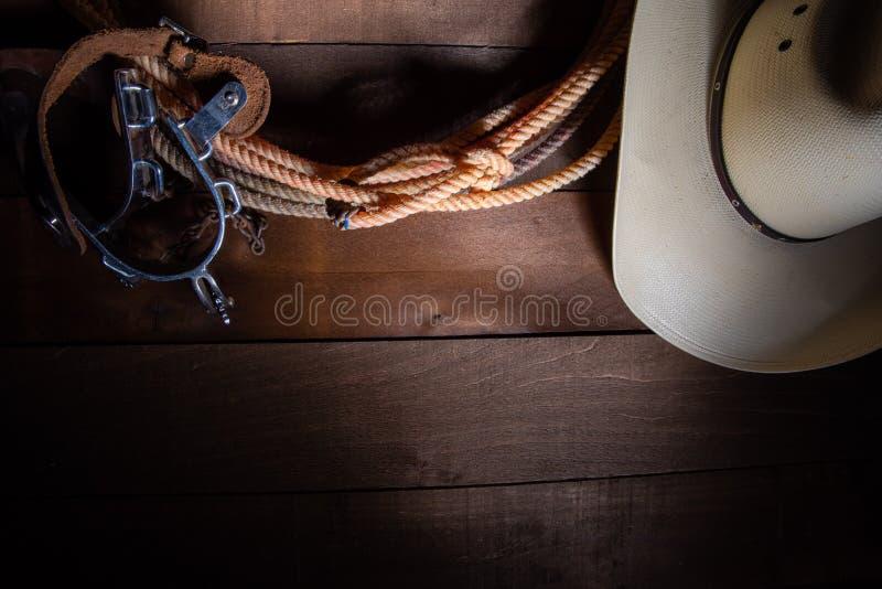 incluing套索踢马刺和一个传统草帽在木板条背景的美国牛仔项目 库存照片