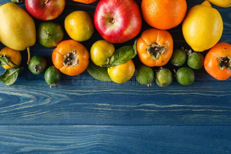 Incluya las verduras orgánicas frescas en el piso de madera blanco con la copia imagen de archivo