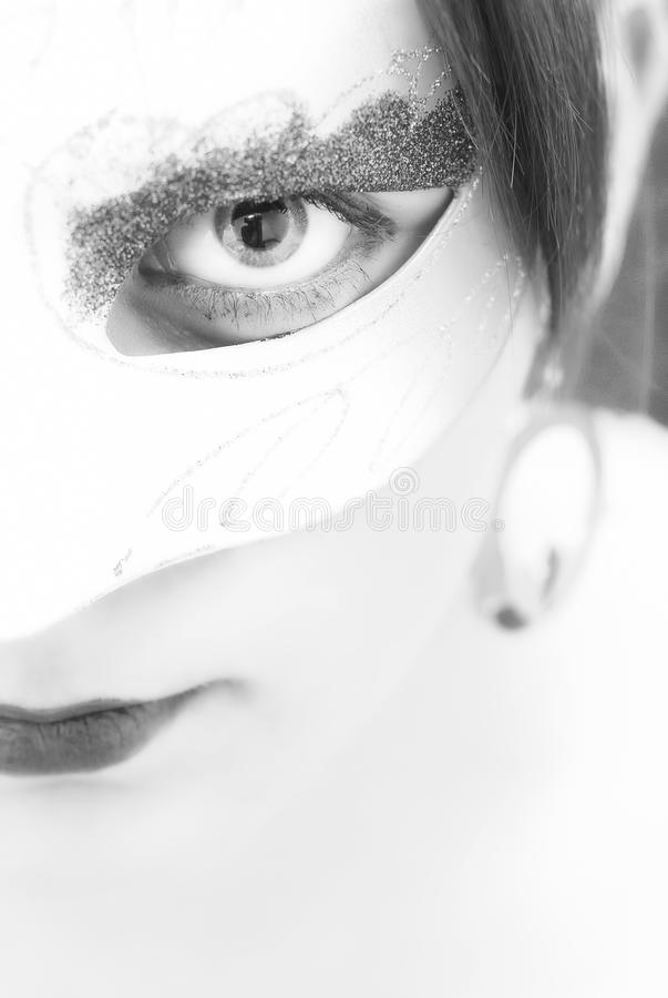 Incognito. High-key portrait of young woman wearing a mask, protecting her identity. Shallow DOF black and white image stock photos