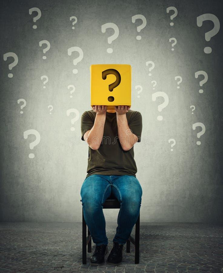 Incognito jonge mens gezet op een stoel die een gele doos met vraagteken in plaats van hoofd houden stock fotografie