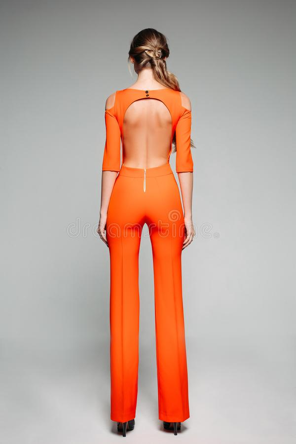 Incognito model in bright orange suit with open back and high heels. Full length back view of fashionable model in casual bright orange overall with open back stock photography