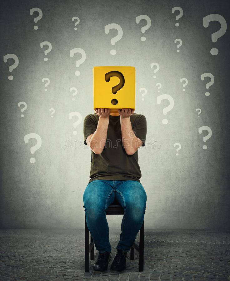 Incognito young man seated on a chair holding a yellow box with question mark instead of head stock photography