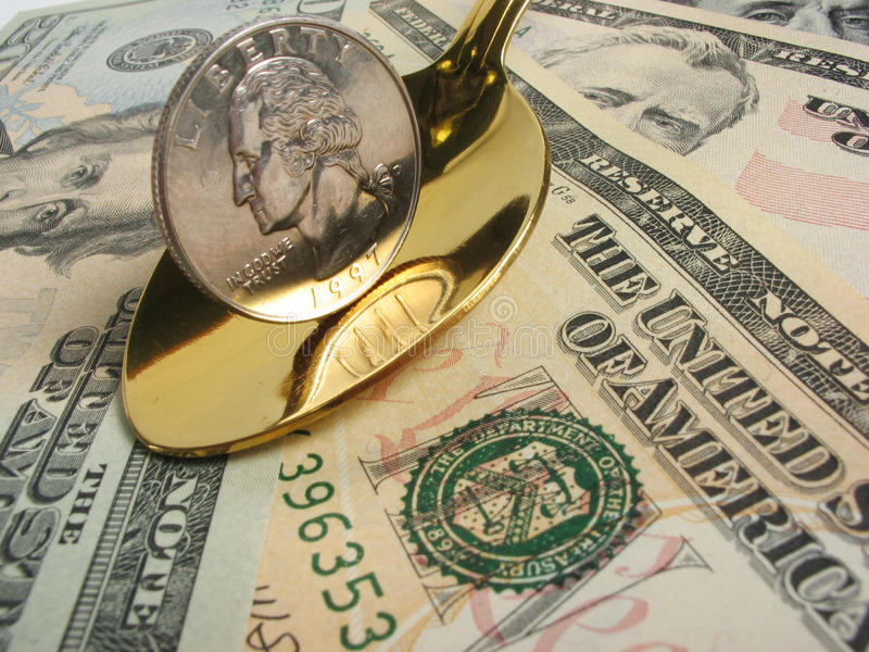 Income. Quarter dollar in gold spoon on a background of dollars stock image
