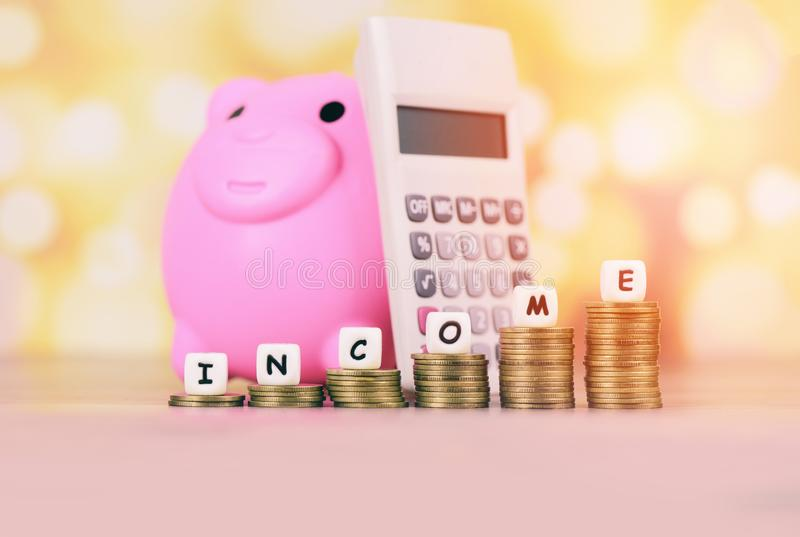 Income growth money coins on table - Pile of golden coin stack step up growing growth saving Concept with piggy bank calculator. Income growth money coins on stock photography