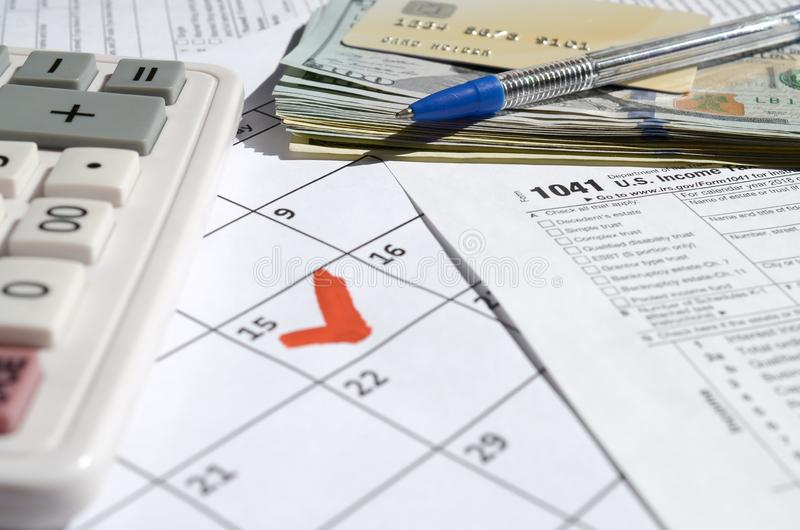 1041 Income Tax Return for Estates and Trusts blank with dollar bills, calculator and pen on calendar page with marked 15th April. Tax period concept. IRS royalty free stock photos