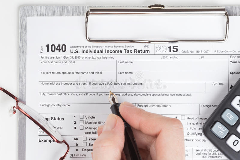 Income Tax Return Form. Female hand filling out Income Tax Return Form stock photos