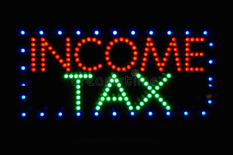 Income Tax Sign. In colorful red, green and blue lights stock image