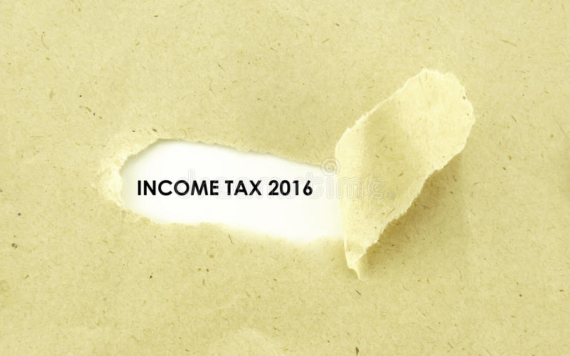 INCOME TAX 2016. Text INCOME TAX 2016 appearing behind torn light brown envelope stock photos