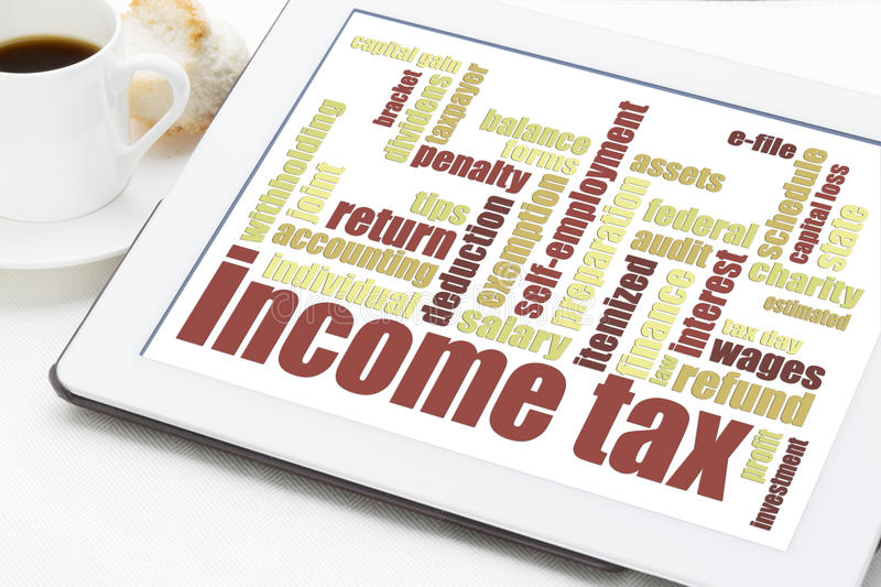 Income tax word cloud. On a digital tablet with a cup of coffee stock photography