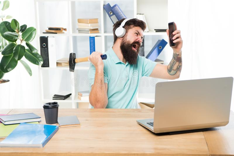 Incoming call. Most annoying thing about work in call center. Annoying client calling. Man bearded guy headphones office. Swing hammer on smartphone. Spoiled royalty free stock photo