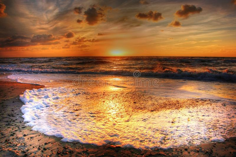Incoming tide at sunset stock photography