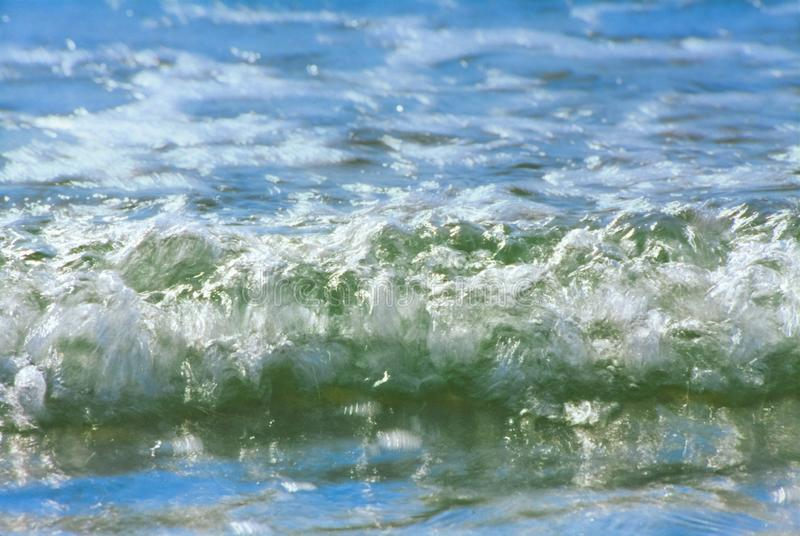 Incoming whitewater wave breaking on the shore royalty free stock photo