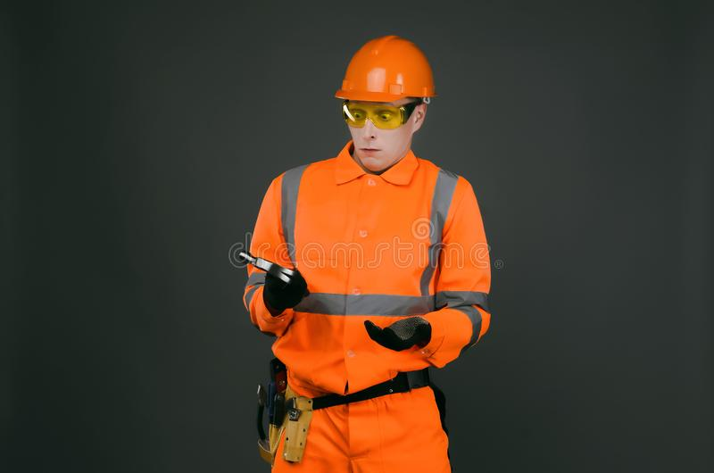 Builder newbie. Incompetent newbie builder worker puzzled looks at the hammer in his hands on gray background. Construction accident stock image