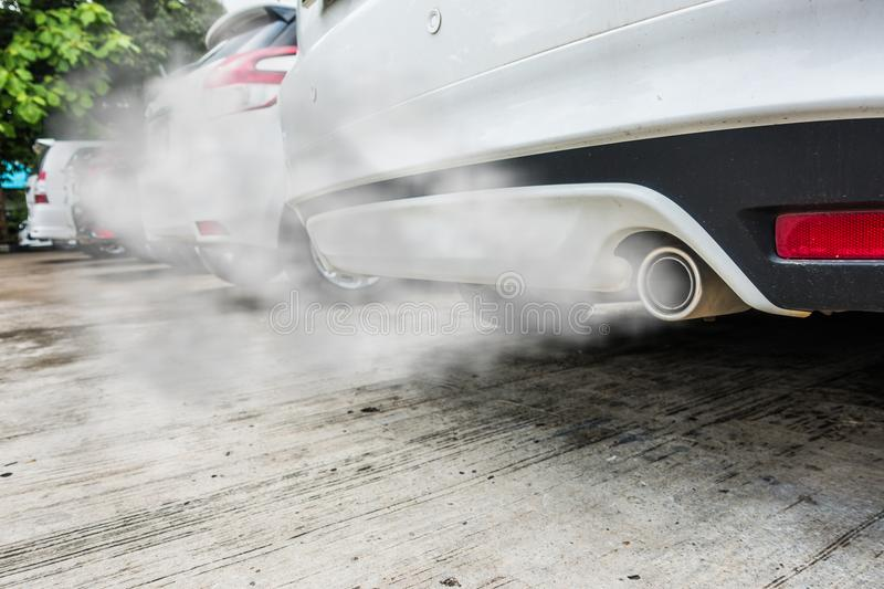 Incomplete combustion creates poisonous carbon monoxide from exhaust pipe of white car, air pollution concept.  stock photo