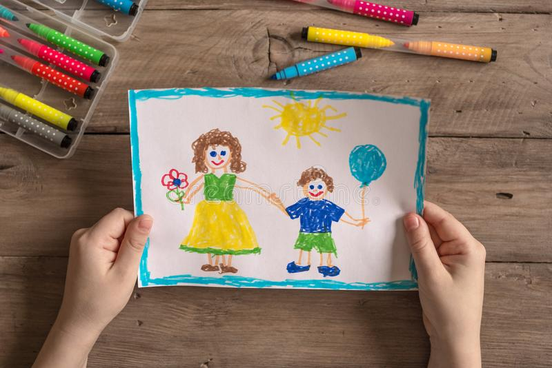 Incomplete family drawing. Children`s drawing of family single mom and son. Incomplete family concept stock photo