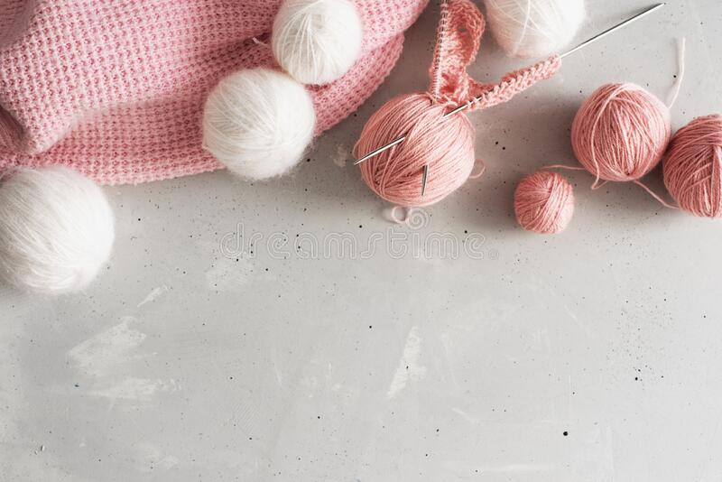 Incomplete knitting project with wooden needles. Light background, pink threads stock image