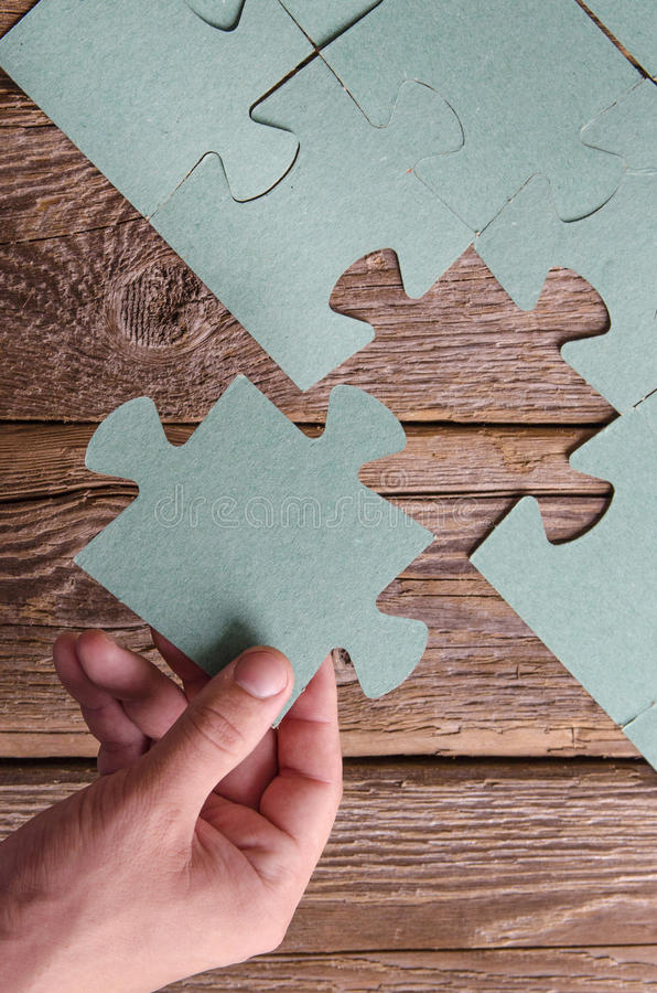 Incomplete puzzles lying on wooden rustic boards. stock images