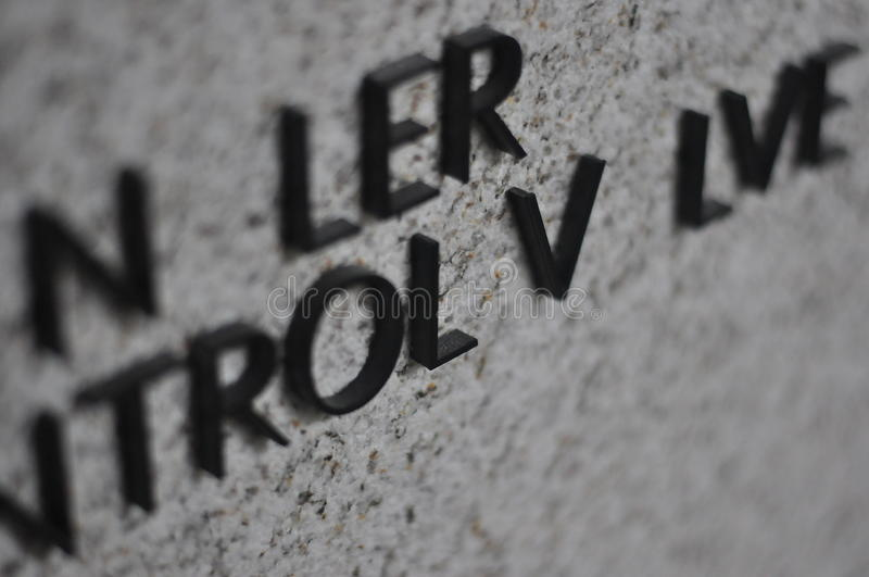 Incomplete Signage. Detail shot of wall aluminium signage with missing letters on stone wall stock photo