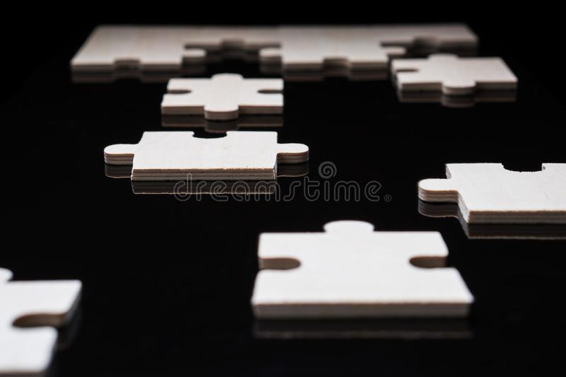 Incomplete wooden puzzles on brown wooden desk stock images