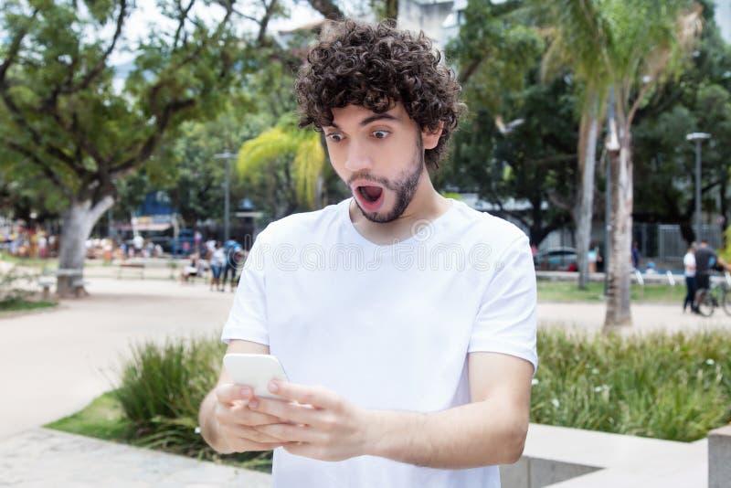 Inconformista adulto joven sorprendido con el teléfono móvil que recibe el mensaje foto de archivo