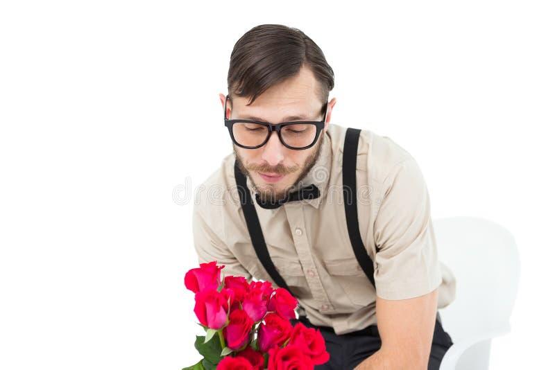 Inconformista afligido Geeky que sostiene rosas imagenes de archivo