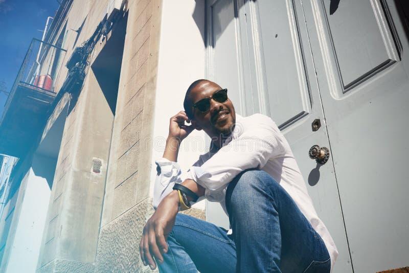 Inconformista afroamericano joven feliz sonriente del hombre en desgaste formal que pasa tiempo en la ciudad imágenes de archivo libres de regalías