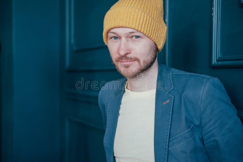 Inconformista barbudo adulto atractivo del hombre en el sombrero amarillo que mira amistoso la cámara en fondo azul de la pared foto de archivo libre de regalías