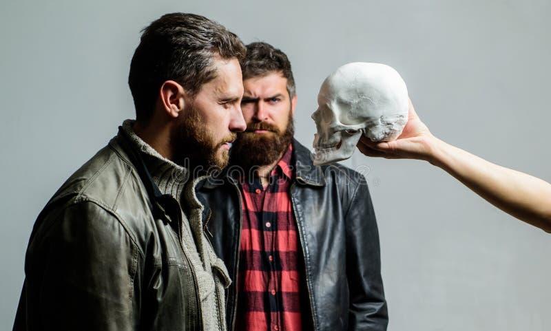 Inconformista barbudo brutal del hombre que mira el símbolo del cráneo de la muerte Supere sus miedos Sea valiente Centrado en la fotos de archivo