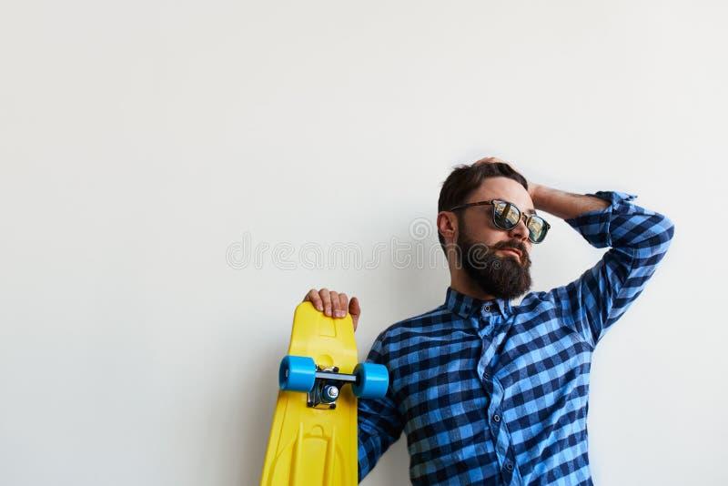 Inconformista barbudo en la camisa a cuadros que sostiene el monopatín amarillo imagen de archivo