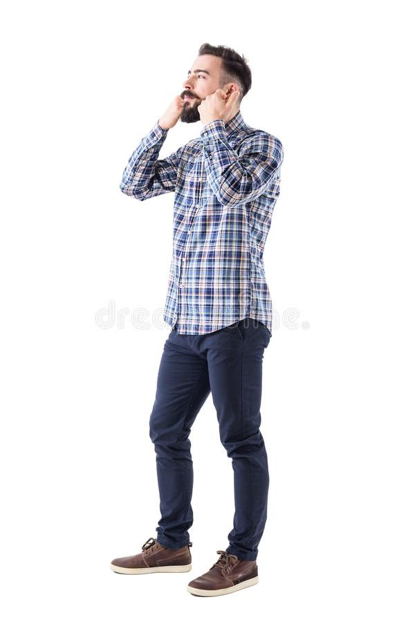 Inconformista barbudo joven en la camisa comprobada que acaricia y que frota ligeramente la barba que mira lejos imagenes de archivo