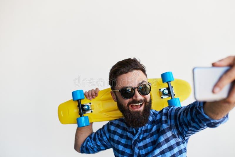 Inconformista barbudo que toma el retrato del selfi con smartphone fotos de archivo libres de regalías