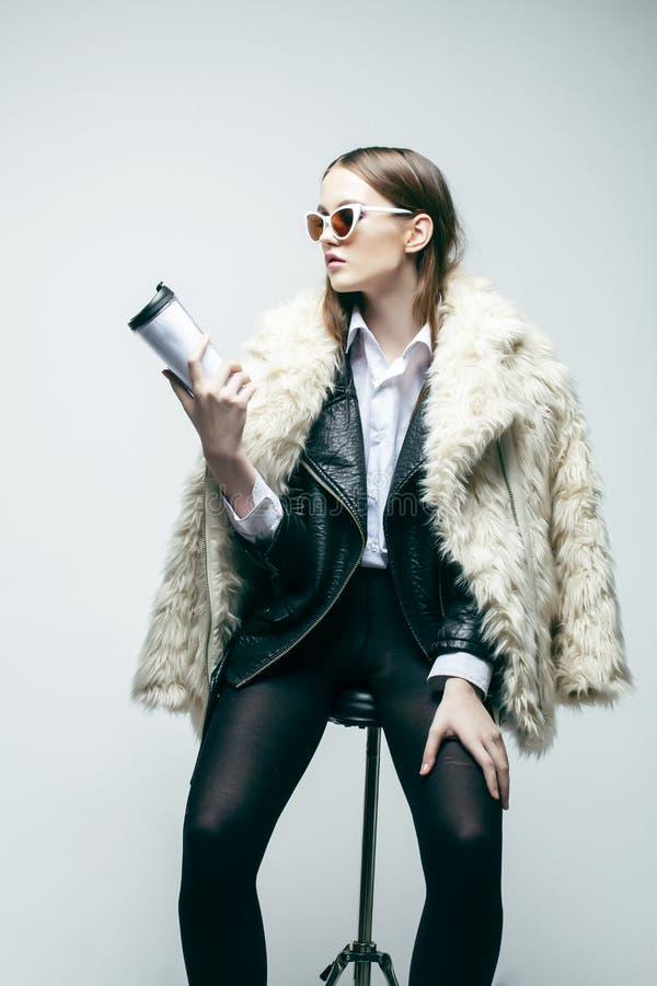Inconformista bonito joven de la muchacha que presenta en estilo de la moda con las gafas de sol que llevan de la taza de café en fotografía de archivo