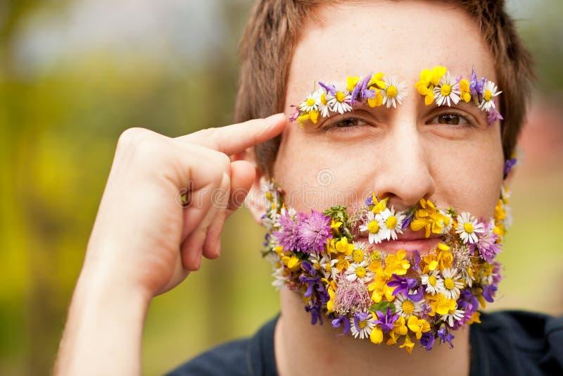 Inconformista cara-cubierto con el pensamiento de las flores foto de archivo