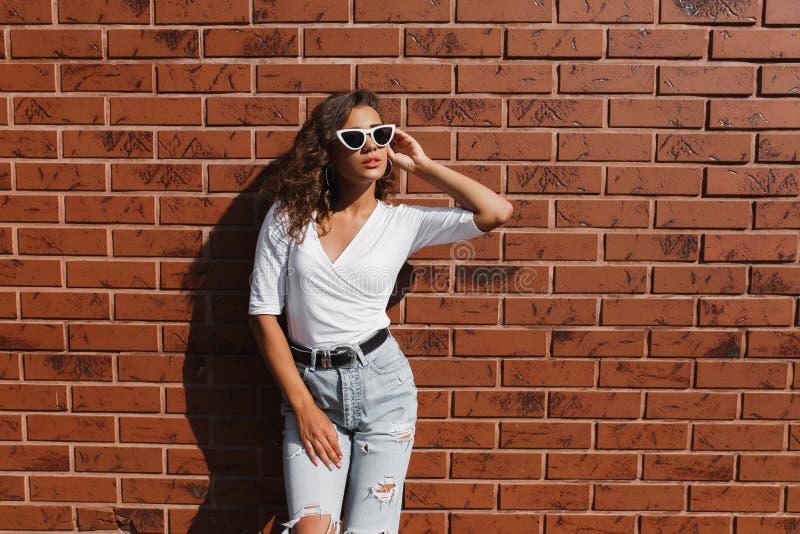 Inconformista elegante de la mujer joven de Attarctive en gafas de sol blancas en pantalones de un dril de algodón del verano y c foto de archivo