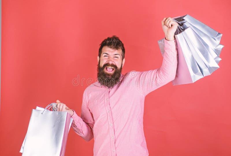 Inconformista en camisa rosada con la barba larga que sostiene los bolsos de plata Hombre barbudo con la cara alegre en backround foto de archivo libre de regalías