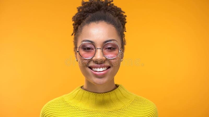 Inconformista femenino alegre en lentes rosadas elegantes en el fondo amarillo, moda fotos de archivo