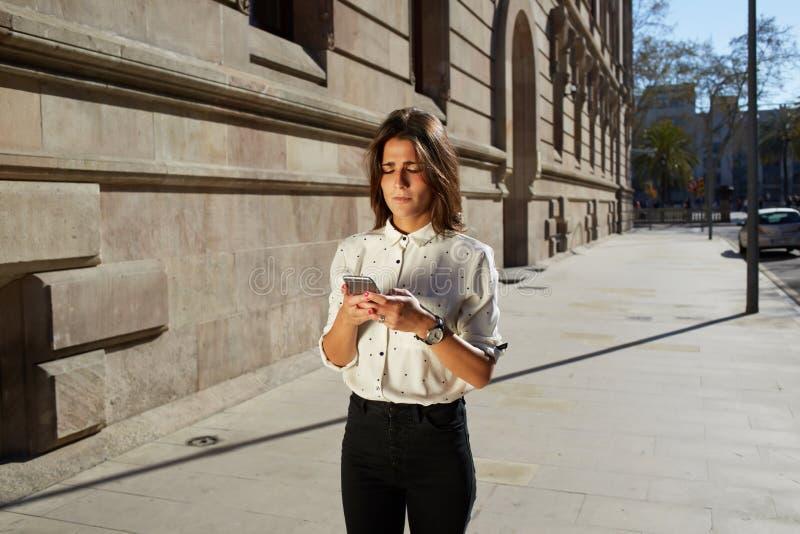 Inconformista femenino elegante que usa su teléfono móvil mientras que camina en el ambiente urbano con el área de espacio grande fotos de archivo