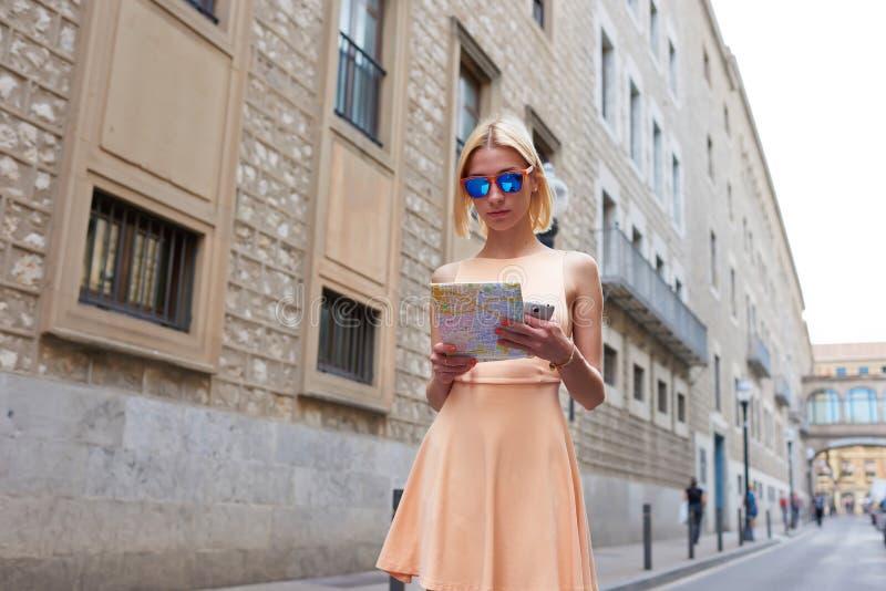 Inconformista femenino en gafas de sol que estudia un mapa mientras que se coloca en el ambiente urbano en día de verano fotos de archivo