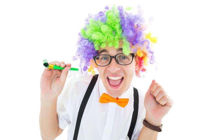 Inconformista Geeky que lleva un cuerno del partido de la tenencia de la peluca del arco iris imagen de archivo